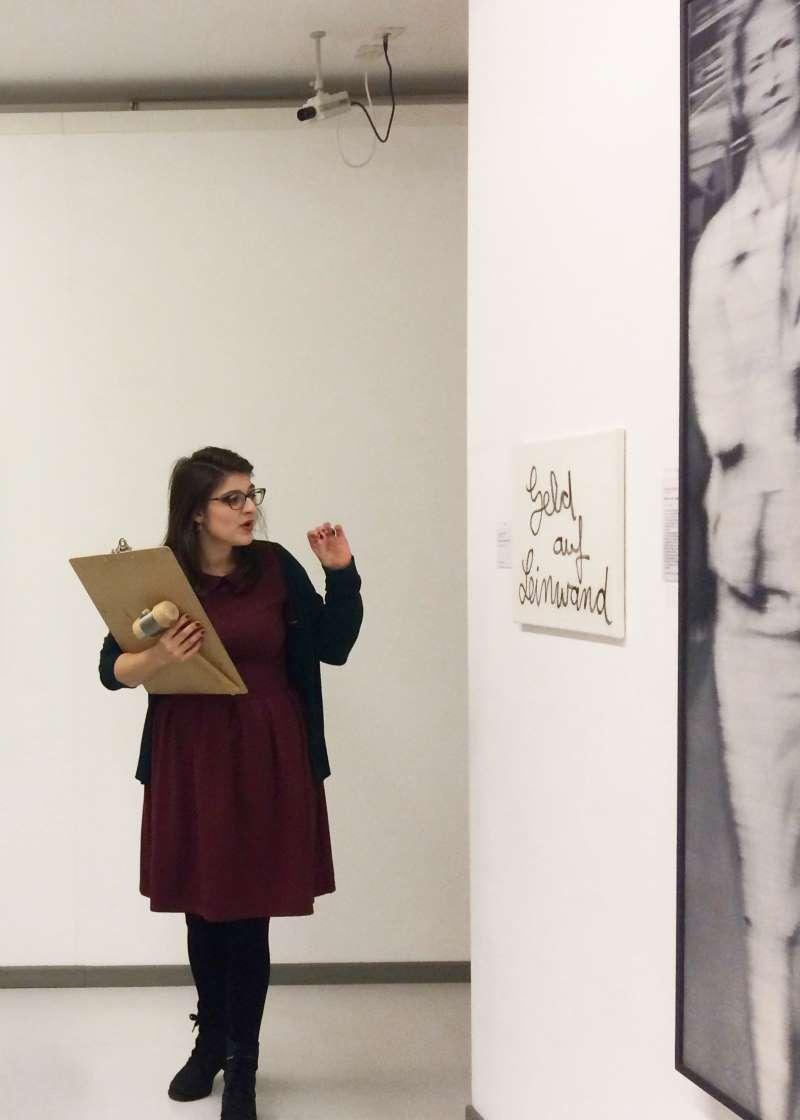 """Die Kunsthistorikerin Linda Schmitz preist das Werk """"Mutter und Tochter"""" von Gerhard Richter an. Es erzielt bei der fiktiven Auktion Warenhauskunst den Höchstpreis. Ludwiggalerie Schloss Oberhausen."""