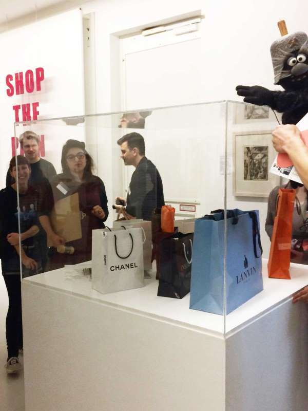 """In Warenhauskunst kommen Kunstwerke unter den Hammer. Hier eine Arbeit von Sylvie Fleury """"Insolvence"""" in der Vitrine, umlagert von Bloggern. Aktion der Ludwiggalerie Schloss Oberhausen"""