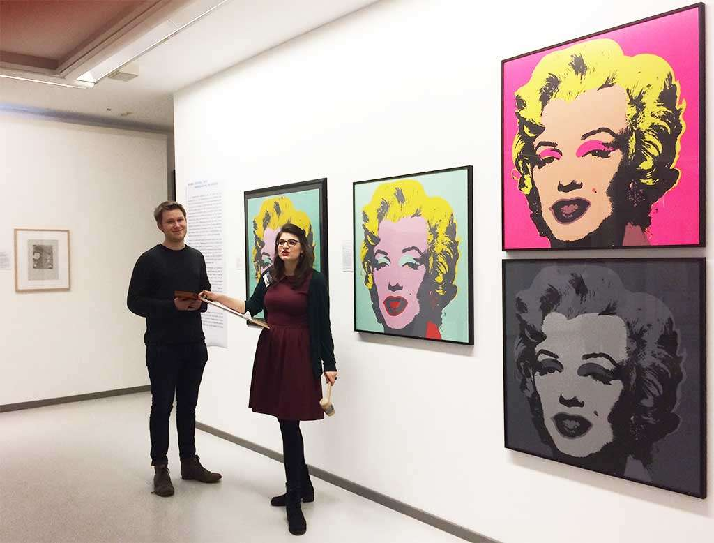 Zwei Personen stehen vor Bildern Andy Warhols, die in Warenhauskunst der Ludwiggalerie Schloss Oberhausen zur Versteigerung stehen. Wer moechte nicht mit Marilyn Monroe nach Hause gehen?