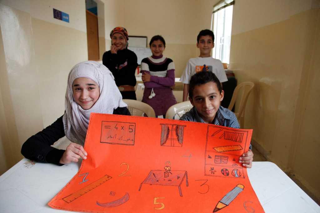 Kinder in syrischer Schule halten ein gebastelten Plakat hoch. Crowdfunding für Bildungsprojekt in Syrien: eine Schule für Kinder.