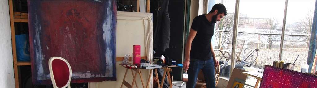 Künstler im Atelier, umgeben von Farben und Leinwand. Syrien Künstler.