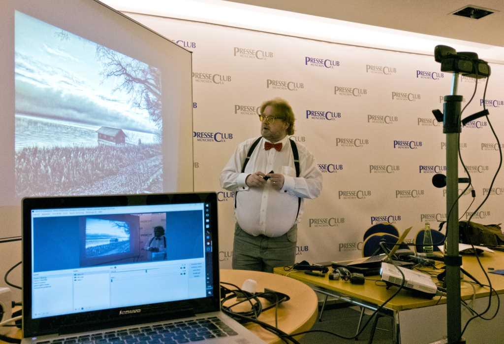 Matthias Lange steht im Presseclub vor einem Bildschirm und erklärt, wie man bessere Fotos mit dem Smartphone fürs Netz macht und nachbearbeitet. Im Vordergrund Bildschirm und technische Geräte zum Streaming des Seminars für den Bloggerclub e.V.