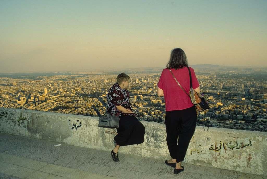 Zwei Frauen blicken auf eine syrische Stadt 1997. Heute ist sie zerstört.