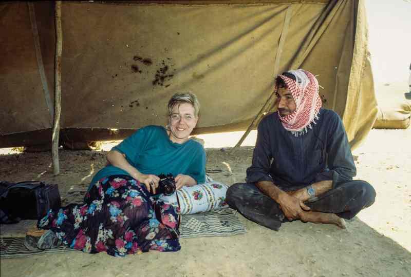 Frau ausgestreckt im Wüstenzelt mit Syrier im Schneidersitz. Besuch 1997.