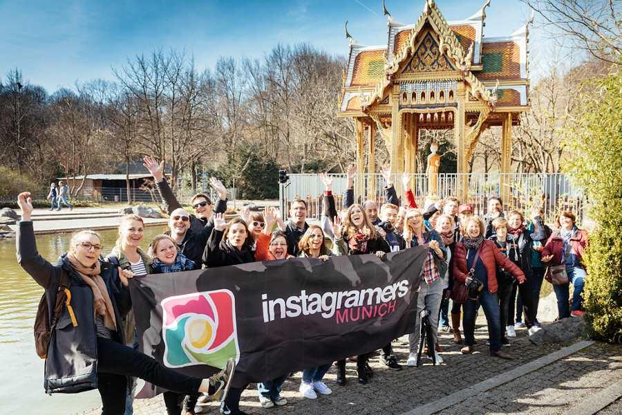 Im Englischen Garten Teilnehmer des #WWIM15MUC, die das Logo der Instagramers Munich hochhalten bei Sonneschein und guter Laune. @igersmunich on tour