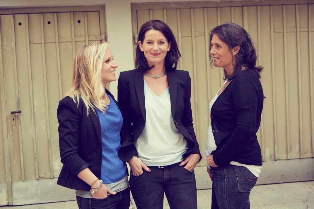 Drei Frauen stehend: Team DEIN MÜNCHEN e. V. von links: Elisa Dudda (Projektkoordination), Mara Bertling (Geschäftsführung und Initiatorin), Katja Schubert (Projektkoordination).