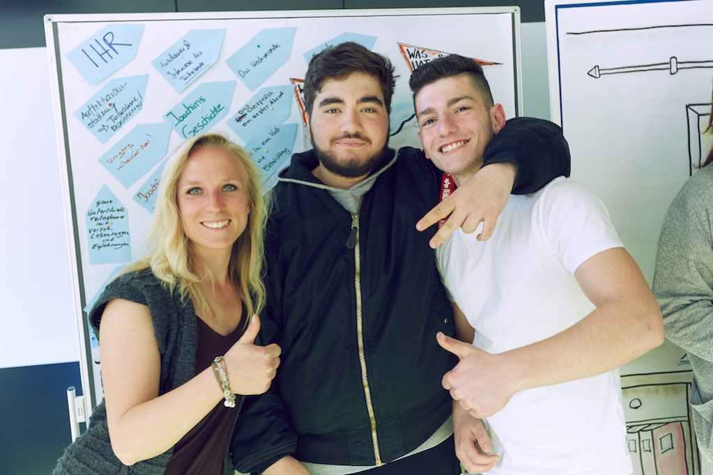 Vor Magnettafel stehen drei Personen, eine Frau (Elisa Dudda) und zwei Jugendliche lächelnd vom Kulturprojekt für DEIN MÜNCHEN e. V.