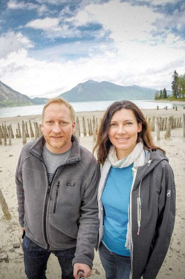 Mann und Frau vor See- und Bergkulisse lachend. Björn Kindler und Anja Sauer von den @igersmunich.