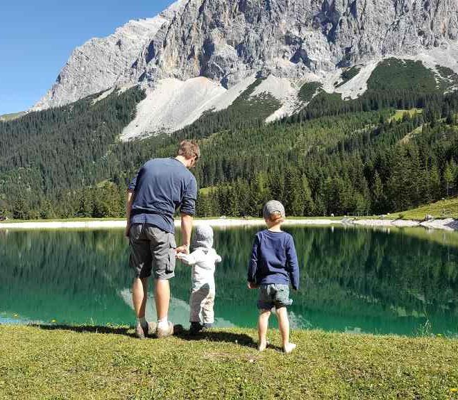 """Alpenkulisse mit See, davor in Rückenansicht ein Vater mit zwei kleinen Kindern in idyllischer Landschaft. Vereinbarkeit von Familie und Beruf ist eine große Herausforderung, aber machbar. Nadja Luge von """"Mama im Spagat"""" im Montagsinterview."""