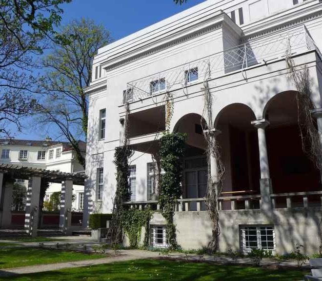 Blick vom Café der Villa Stuck auf die Künstlervilla von draußen bei herrlichem Sonnenschein im April.
