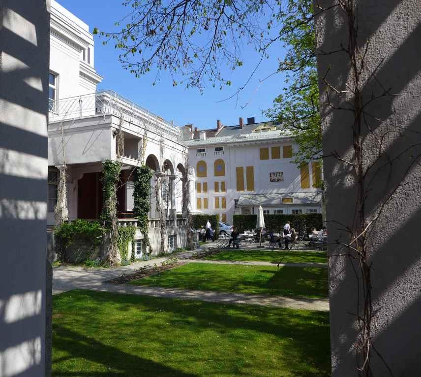 Blick von der Pergola des Künstlergartens der Villa Stuck auf die Villa und das Café bei bestem Aprilsonnenschein.