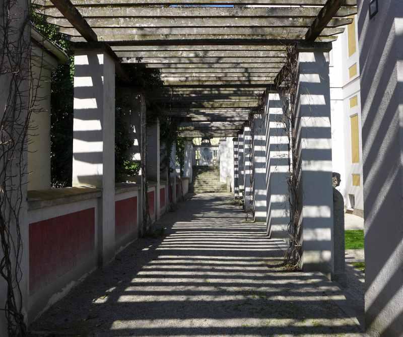 Blick von der Terrasse des Künstlergartens auf die Pergola der Villa Stuck bei Sonnenschein. Tolles Licht- und Schattenspiel.