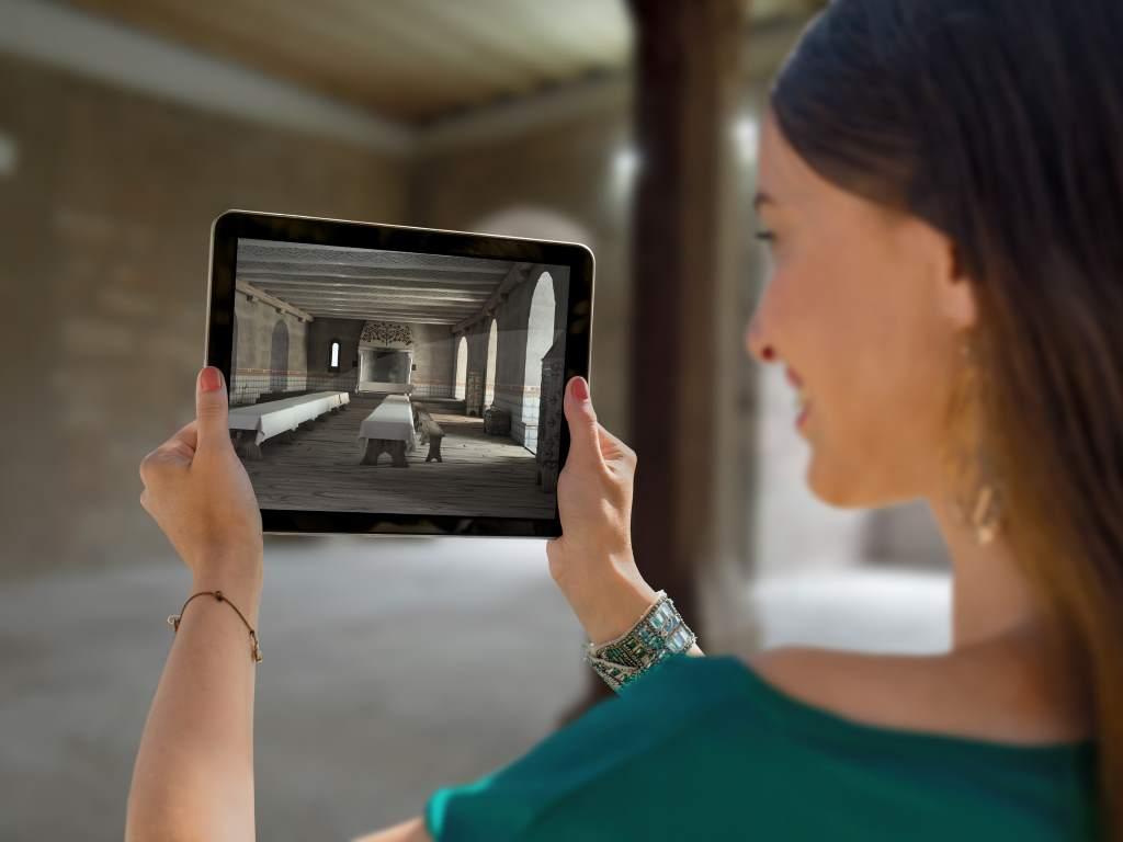 Frau hält Tablet, das via Augmented Reality das Interieur der Burg im Mittelalter zeigt. Cadolzburg #HohenzollernWalk