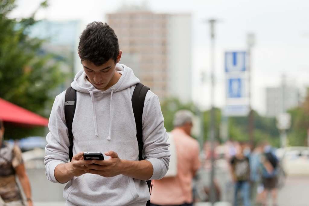 Junger Mann auf Handy im Stadtverkehr blickend. Die Münchner Stadtbibliothek stellt vieles digital zur Verfügung. digitale Projekte via eBook. elearning-Plattform