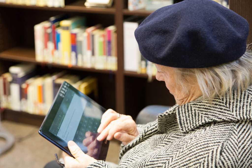 Alte Dame am Tablet in der Münchner Stadtbibliothek in Sendling. Visualisiert die Digitialisierung als Chance für Bibliotheken.
