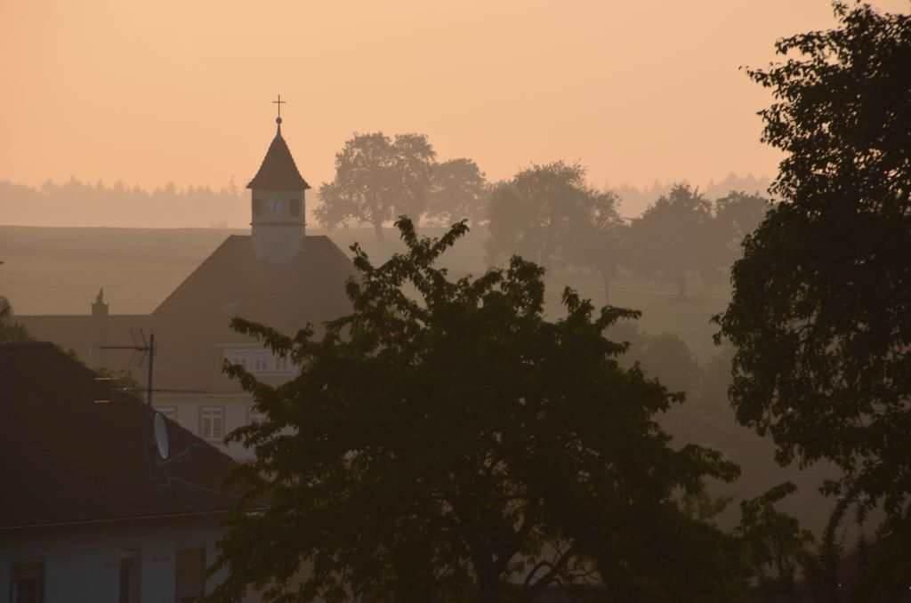 Das Dorf Balsbach im Odenwald am frühen Morgen fotografiert: diesog. gelb dunkle und vernebelte Ansicht auf die Kirche des Dorfes