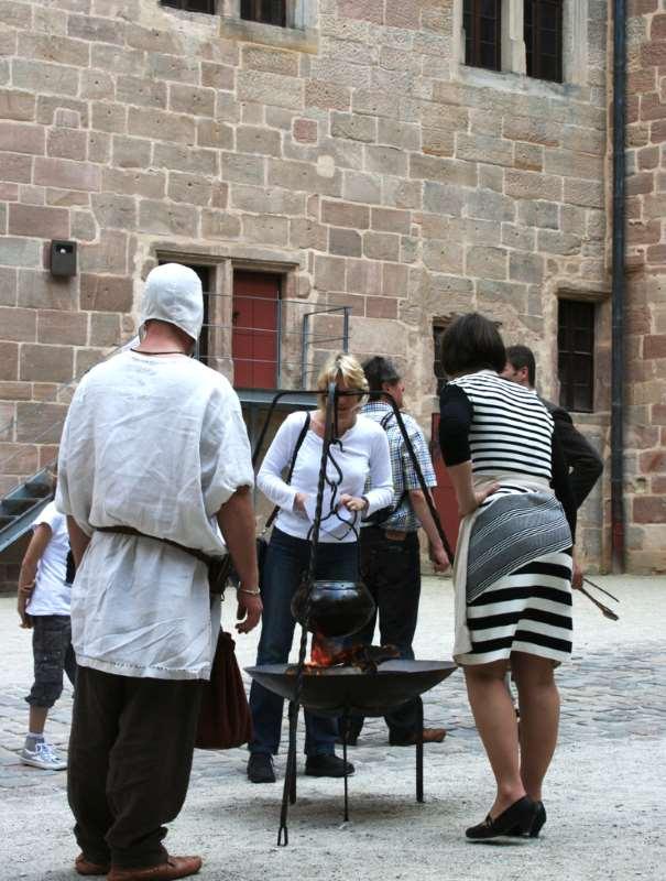 Dreibein mit Topf, davor jemand in spätmittelalterlicher Kluft gekleidet und Menschen, die in den Topf blicken. Kochworkshop auf der Cadolzburg. Kochen im Mittelalter.