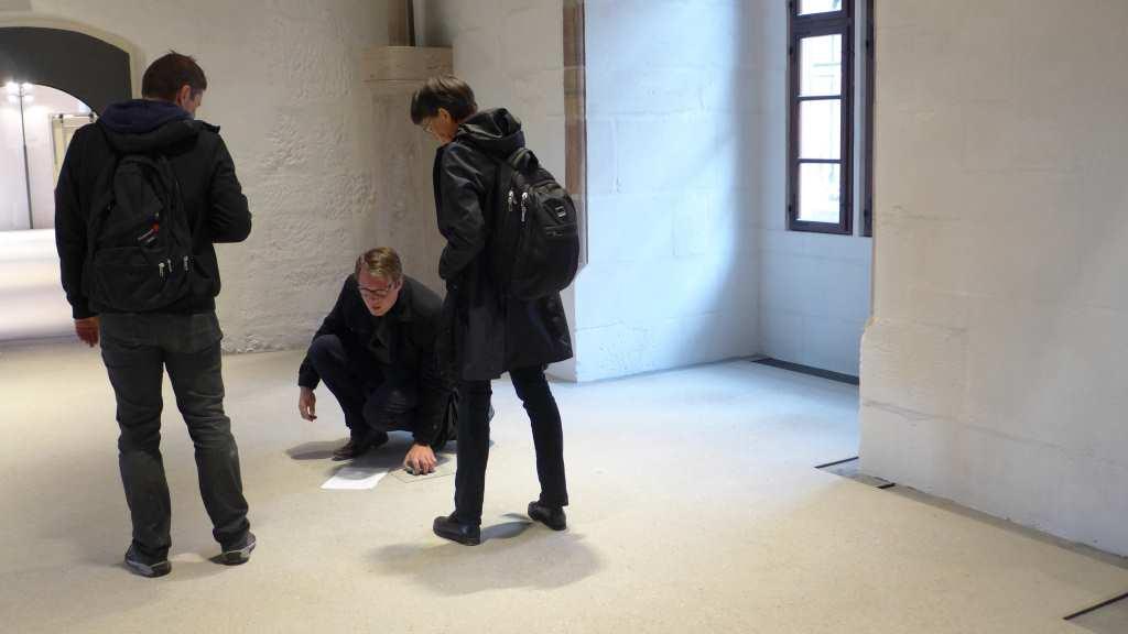 Drei Leute überprüfen Bodenplatte im Erkersaal der Cadolzburg.