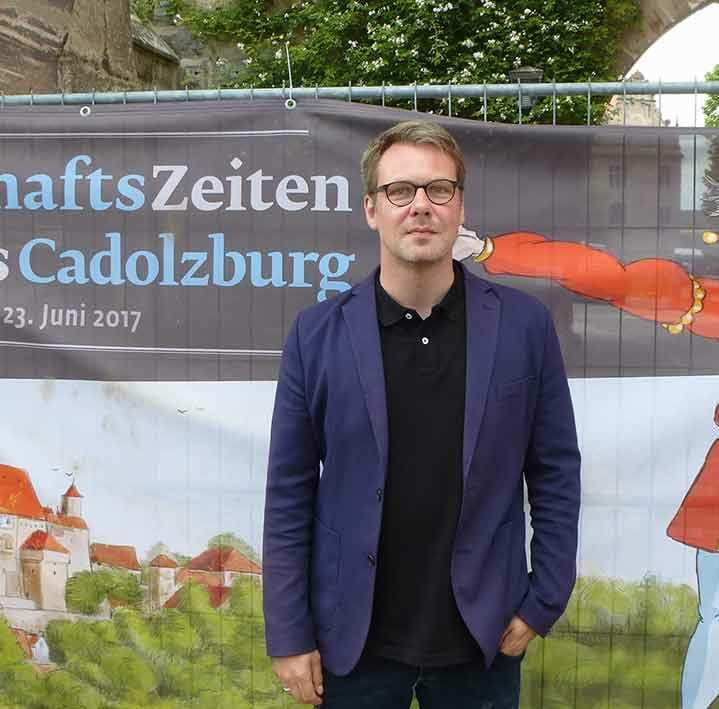 """Sebastian Karnatz stehend vor einem Plakat der Ausstellung """"HerrschaftsZeiten"""" der Cadolzburg."""
