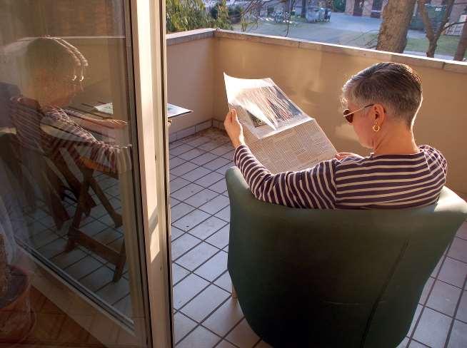 Kaltmamsell auf dem Balkon lesend mit dem Rücken zu uns gewandt.