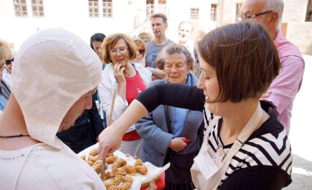 Menschen um ein Tablett mit Krapfen gescharrt, die nach mittelalterlichem Rezept erstellt sind. Kochen im Mittelalter auf der Cadolzburg.