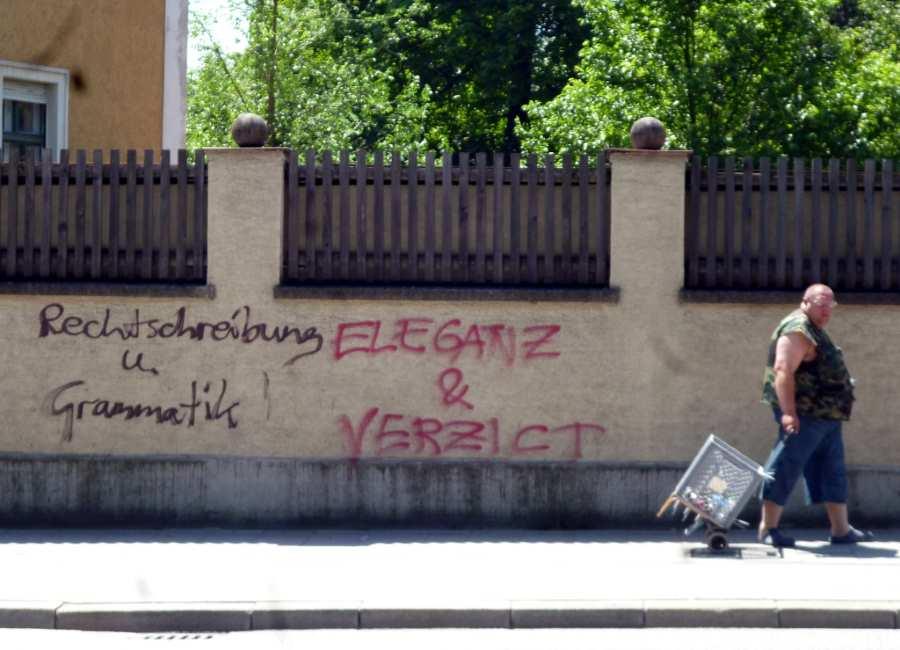 Straßenszene, beschmierte Wand mit Aufschrift Eleganz Grammatik, Mann mit Einkaufsanhänger geht vorbei. Vorspeisenplatte