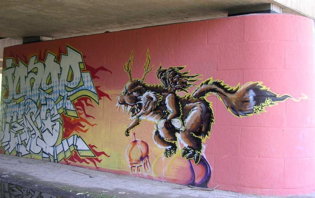 Street art in München an der Isar: Ein Wolpertinger, der wie King Kong auf den Türmen der Frauenkirche hockt und statt der weißen Frau eine Weißwurst würgt. Gefunden von Kaltmamsell von Vorspeisenplatte.