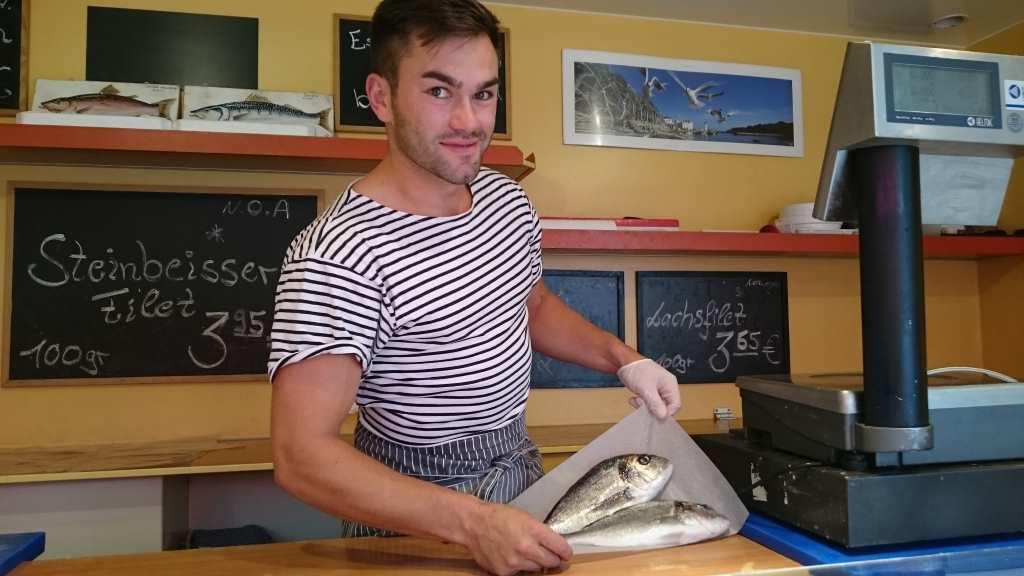 Fischverkäufer zeigt 2 Doraden.