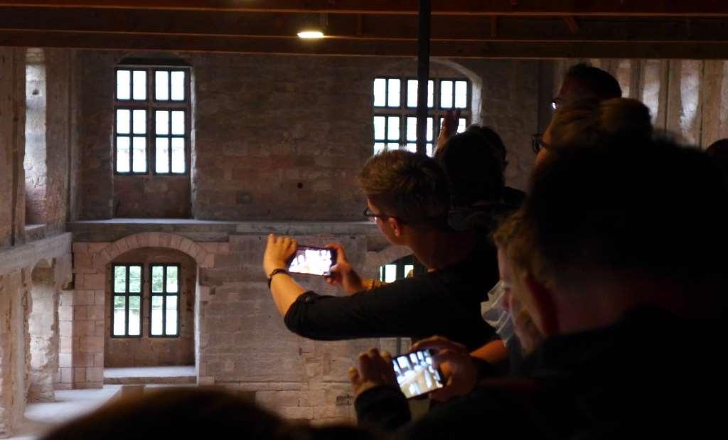 Teilnehmer des #HohenzollernWalk-s fotografieren mit Handys das Neue Schloss der Cadolzburg.