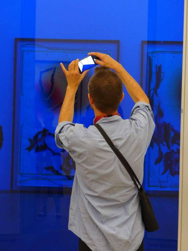 Blogger vor blauer Glaswand, dahinter Bilder von Kerstin Brätsch. Installationsansicht Illuminations im Museum Brandhorst. #openbrandhorst17
