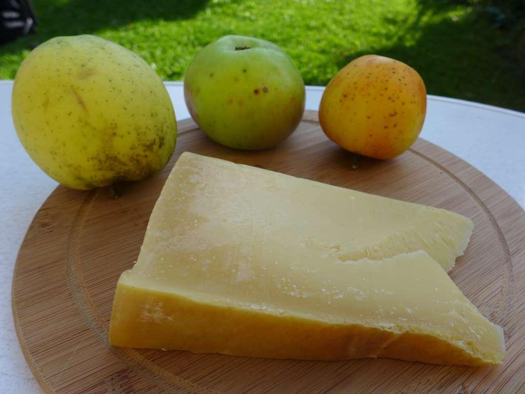Blick auf Brett mit drei Äpfeln unterschiedlicher Sorte und den Schleißheimer Parmasan-Käse.