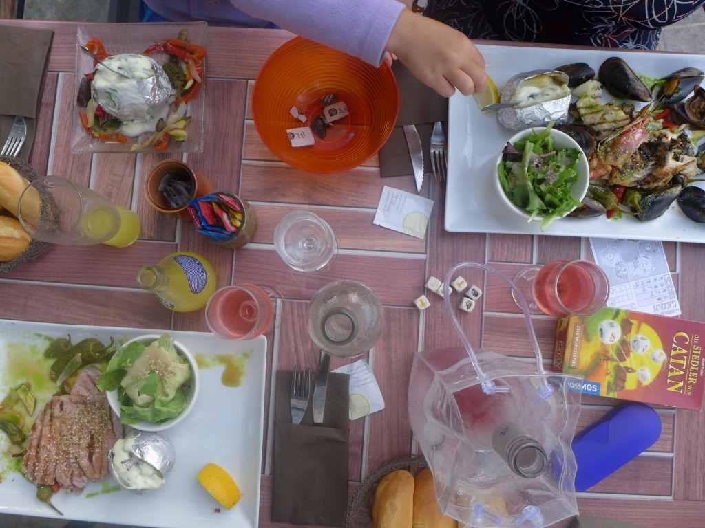 Aufsicht auf gedeckten Tisch mit verschiedenen Tellern, darauf Fisch, Muscheln und Garnelen. Kinderhand mopst sich etwas von einer Kartoffel. Spiel, Wein und Gläser. Unser Kulturblick auf die französische Kultur geht durch den Magen. Blogparade #KultBlick