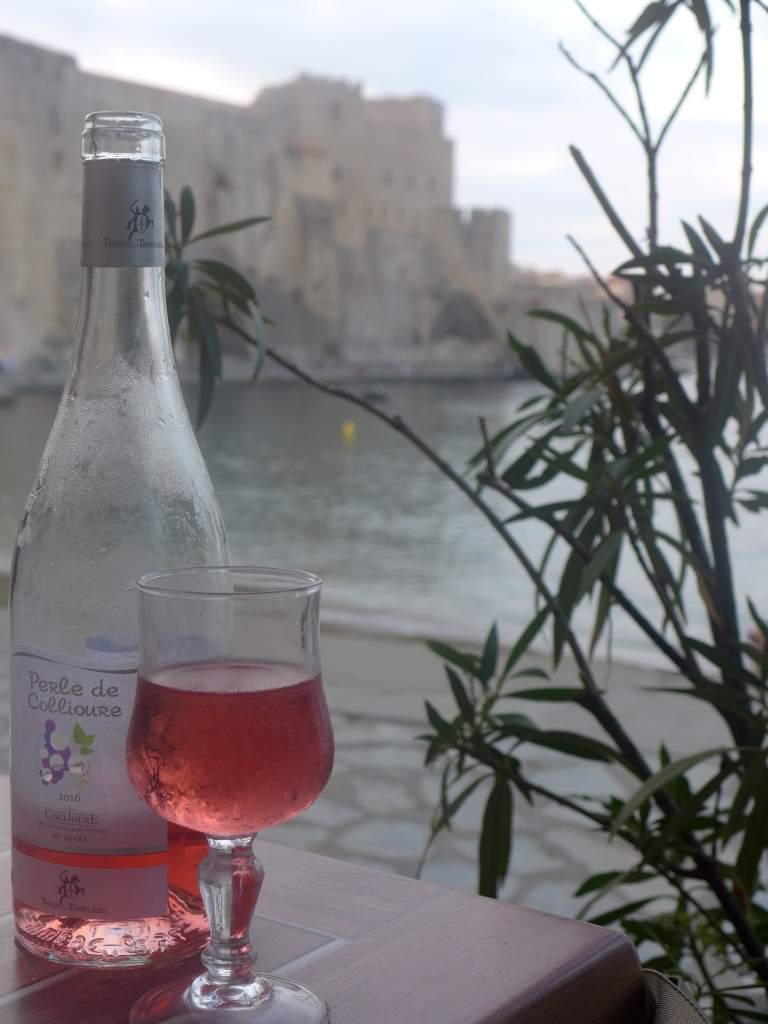 Weinflasche auf Tisch, im Hintergrund die Festung von Colliure, Südfrankreich.