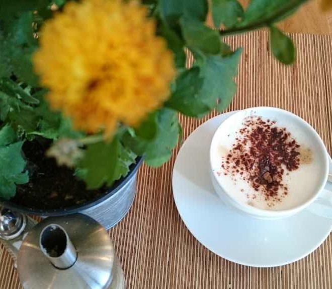 Tasse Cappuccino mit Blumen auf den Tisch. Moment der Muße am #WMDEDGT