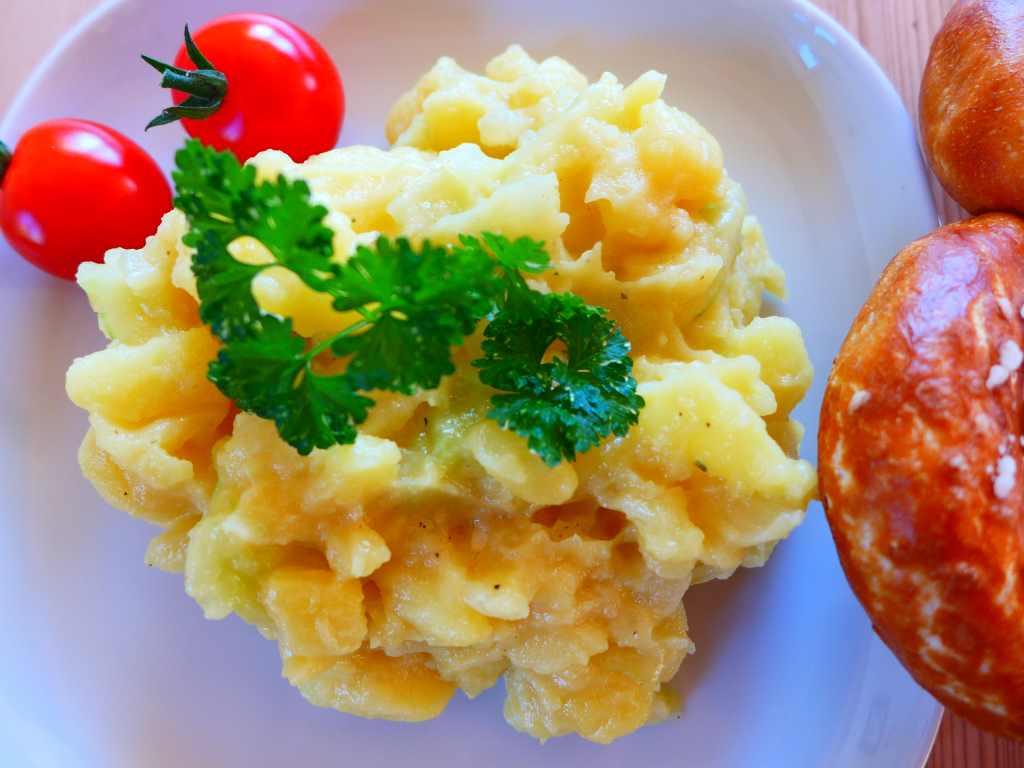 Teller mit Kartoffelsalat, Tomaten und Brezn.
