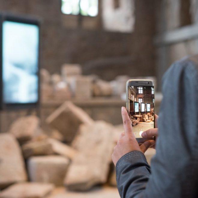 Besucherin fotografiert Installation im Neuen Schloss der Cadolzburg. Im Vordergrund die scharfe Handyeinstellung, die Installation im Hintergrund verschwommen. aufgenommen während des Hohenzollernwalks auf der Cadolzburg. Soziale Medien im Museum funktionieren wunderbar.