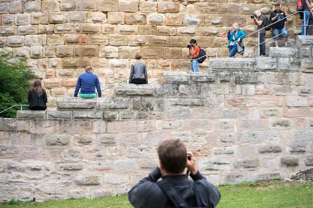 Treppe einer Burg. Instagrammer in Rückenansicht zum Fotografen auf Brüstung sitzend. HohenzollernWalk befördert Partizipation im Museum.