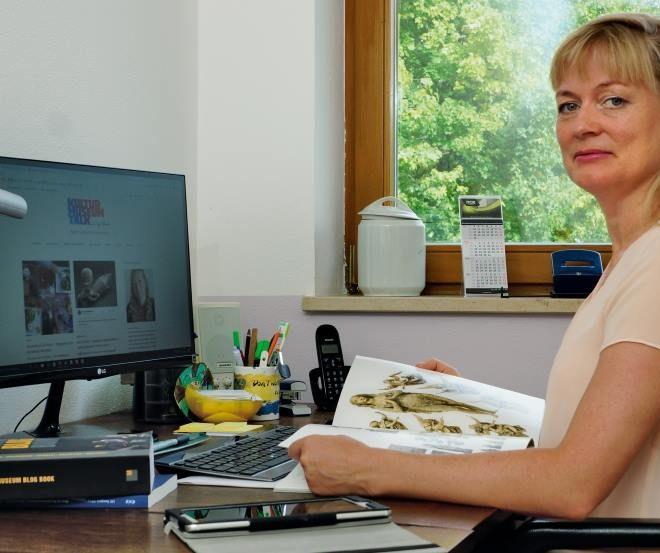 Die Kunsthistorikerin und Kulturbloggerin Tanja Praske bei der Arbeit am Schreibtisch mit Katalog, Büchern und Tablet.