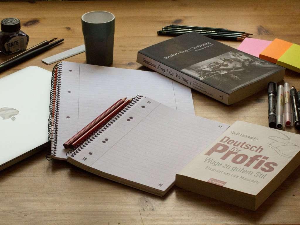 Schreibutensilien auf Tisch ausgebreitet, mit Feder, Tintenfass, Buch und Blog - illustrierend zu Julian Stalter-s Gastbeitrag zu den Schreibtipps für Blogger.