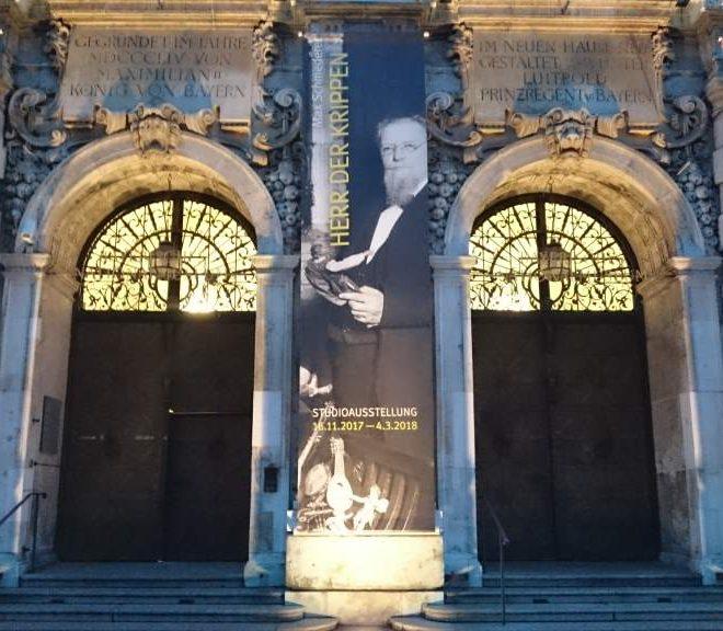 """Eingang des Bayerischen Nationalmuseums am Abend mit Banner der Ausstellung """"Herr der Krippen - Max Schmederer. Sammler, Stifter und Visionär"""". Läuft noch bis zum 4. März 2018."""
