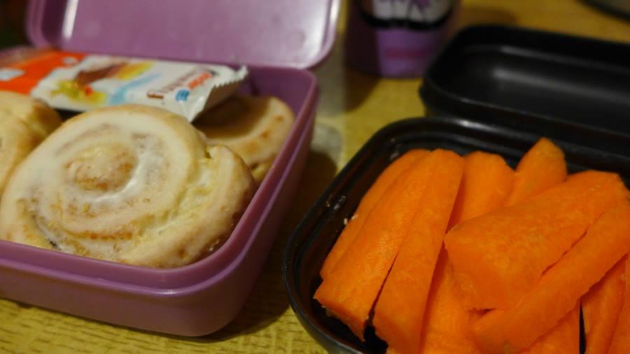 zwei Tupperdosen mit Zimtschnecken und Karotten. Proviant für die Skipiste.