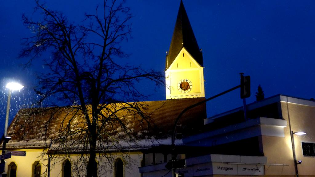 Kirche im Dunkeln in der Früh an Faschingsmontag bei Schneefall.