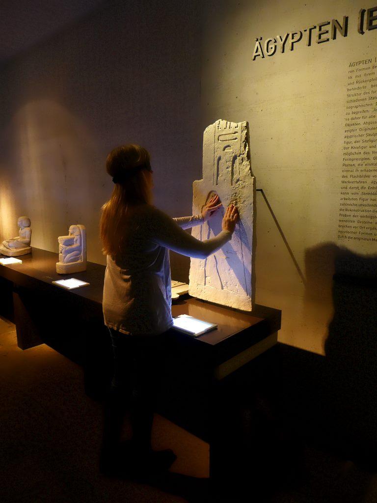 Tanja Praske steht im Ägyptischen Museum München vor einem Flachrelief, eine Replik, und ertastet es.