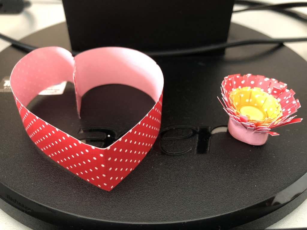 Bildschirmfuß mit rotem Herzchen und rot-gelber Papierblüte.