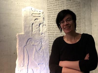 """Porträtaufnahme von Roxane Bicker, Museumspädagogin am Archäologischen Museum München. Sie steht vor einem Relief im Raum """"Ägypten (er)fassen""""."""