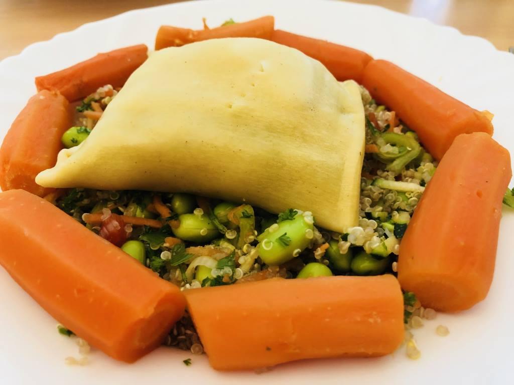 Teller mit Salat, Karotten und Maultasche.