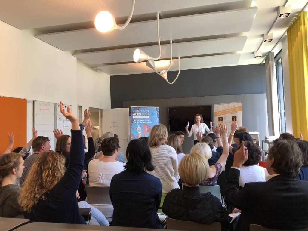 Sitzende Menschen im Raum, Lina Timm auf dem Podium zugewandt. Isarcamp zur Münchner Webwoche 2018 - eine ideale Gelegenheit für Bloggervernetzung.