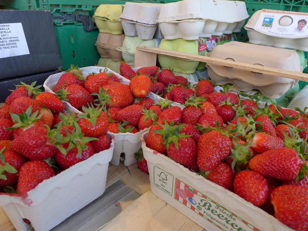 Marktstand im Vordergrund Erdbeeren in Pappschälchen und Eierkartons. 12von12