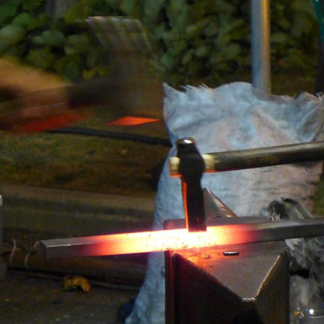 Glühendes Eisen auf einem Amboss. Der Hammer schlägt zu. Steht symbolisch für Blogparaden in der Kultur - Chancen, Risiken und Learnings.