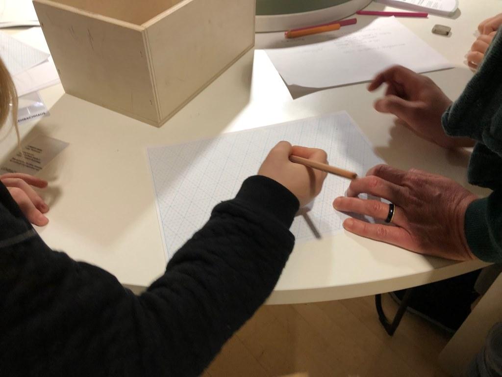Kinder- und Erwachsenenhände, weißes Blatt Papier sind dabei etwas zu malen.